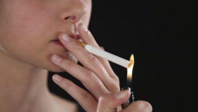 Поджигает сигарету